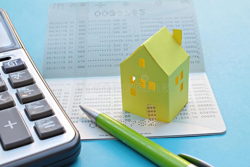 储蓄帐户存款簿、计算器、笔和黄色纸房子蓝色背景的 免版税库存图片