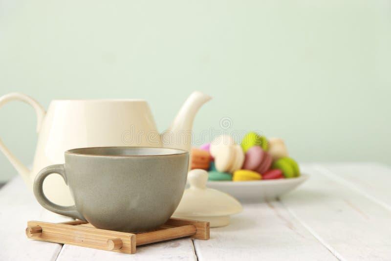 储蓄照片:茶和轻拍在白色b的五颜六色的蛋白杏仁饼干 免版税库存图片