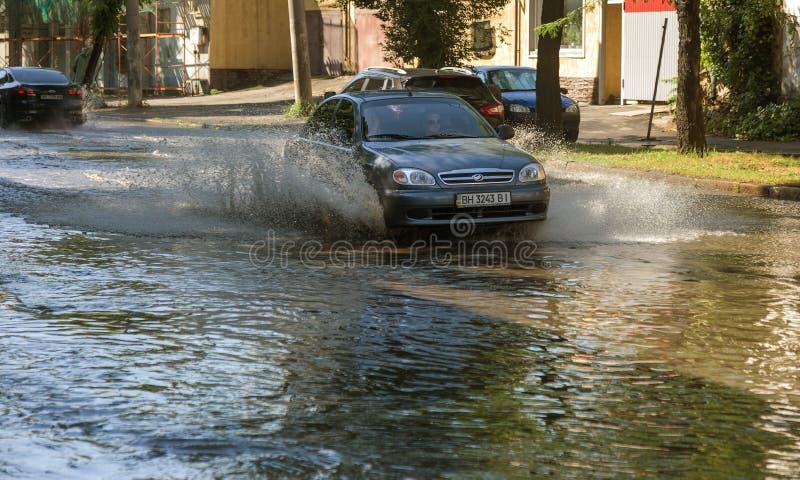 傲德萨,乌克兰2018年7月-3 :驾驶在一条被充斥的路的汽车在雨造成的洪水期间猛冲 在水的汽车浮游物,充斥st 库存图片