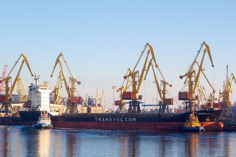 傲德萨-乌克兰:2017年1月2日:一艘抬举费力的海洋船乘猛拉小船护航在港口外面 傲德萨港  库存照片