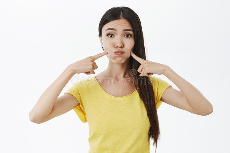 傻的女性和逗人喜爱的女性模型画象在噘嘴黄色的T恤杉的屏住呼吸和戳与索引的面颊 库存图片
