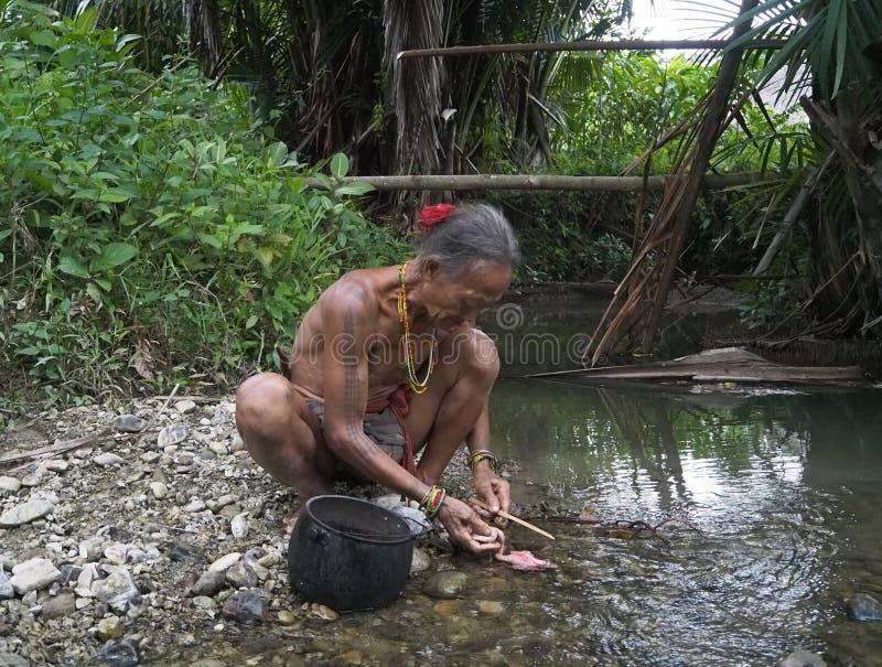 僧人清洁鸡内脏在河 库存图片