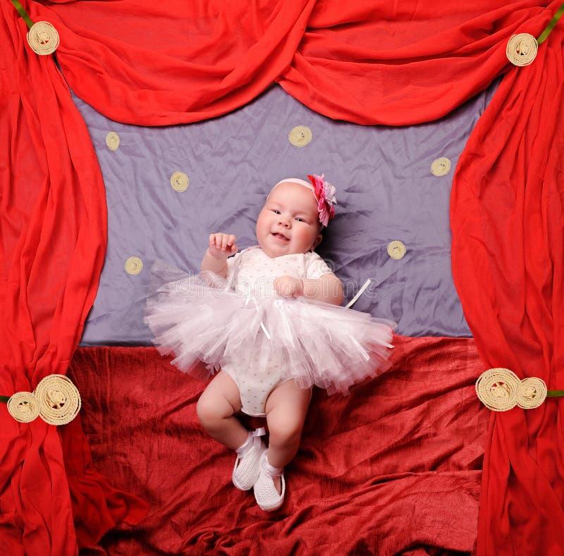 婴儿女婴佩带的白色芭蕾舞女演员芭蕾舞短裙和钩针编织的芭蕾拖鞋 库存图片