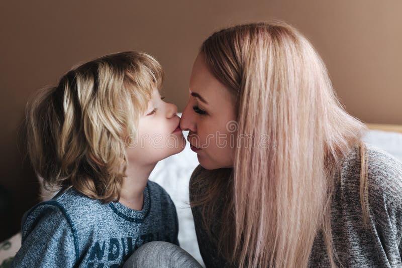 儿子亲吻他的母亲 两个绿色牛仔裤妈妈儿子顶层佩带 日愉快的母亲s 在家拥抱她的孩子的母亲 免版税库存照片