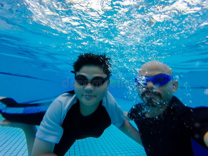 儿子和爸爸在水池,爸爸游泳在水面下教他的儿子潜水在水下 库存图片