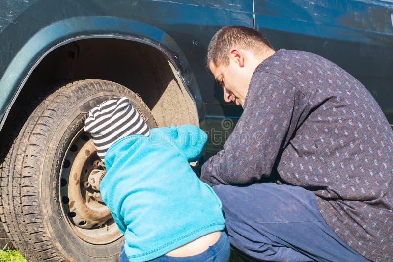 儿子帮助爸爸修理汽车 库存图片