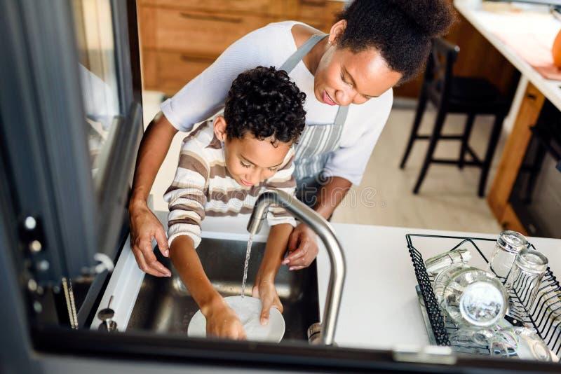 儿子帮妈妈洗碗 免版税库存照片