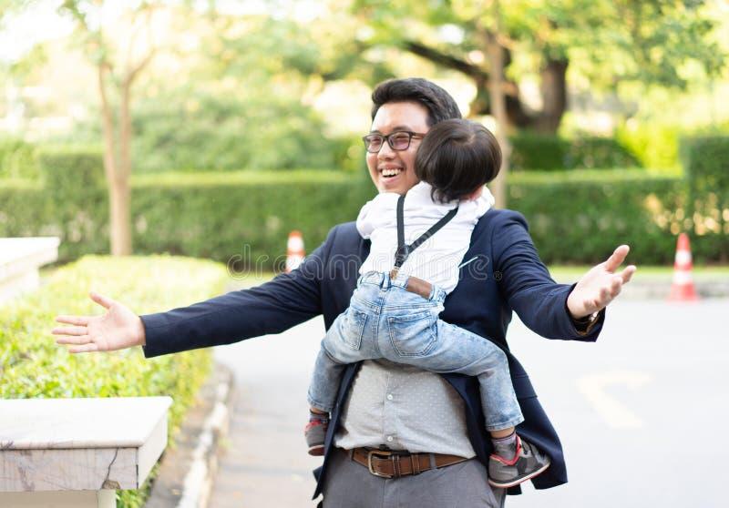 儿子拥抱他的父亲和微笑与偶然衣服在公园 免版税库存照片
