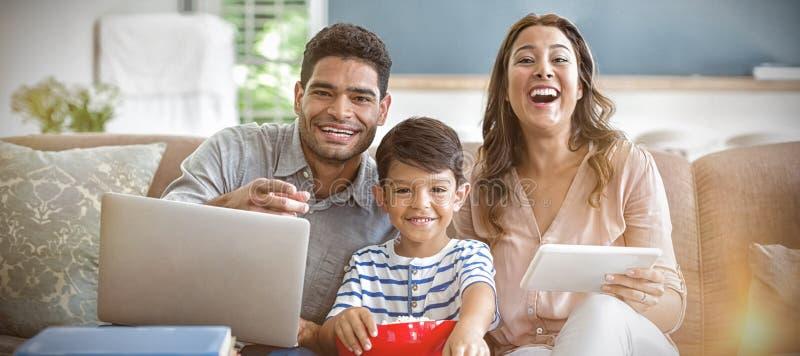 儿子观看的电视,当父母使用膝上型计算机和数字片剂在家时 库存照片