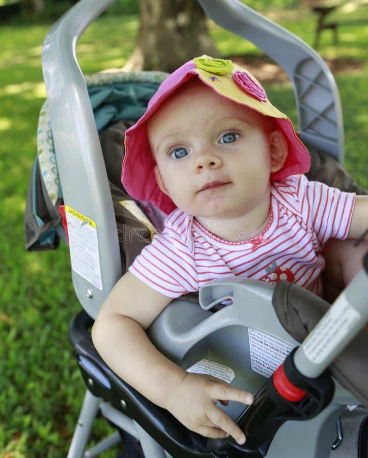 婴儿推车的可爱的女婴 库存照片