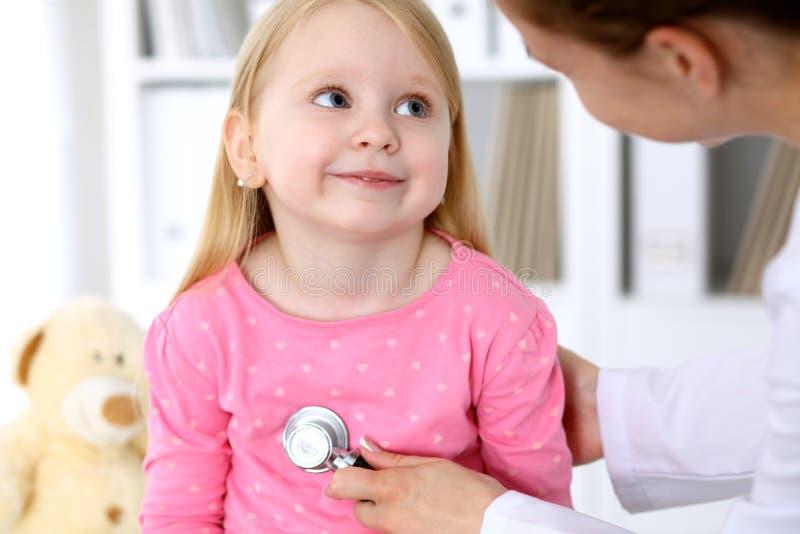 儿科医生在医院照顾婴孩 小女孩是由医生审查由听诊器 胳膊关心健康查出滞后 免版税库存照片