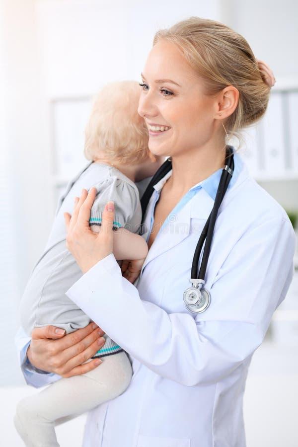 儿科医生在医院照顾婴孩 小女孩是由有听诊器的医生审查 免版税库存照片