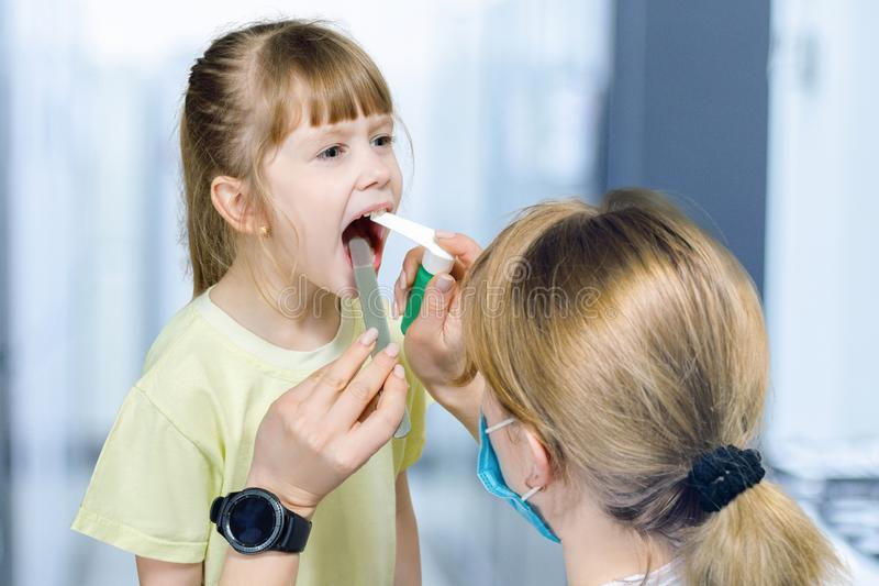 儿科医生对待一个小孩子的喉头 库存图片