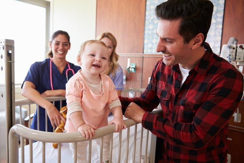 儿科医生参观的父母和孩子在医院病床上 库存照片
