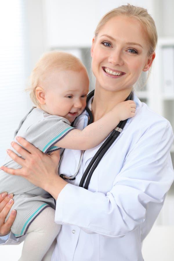 儿科医生在医院照顾患者 女性医生拿着小孩女孩在手 免版税库存照片