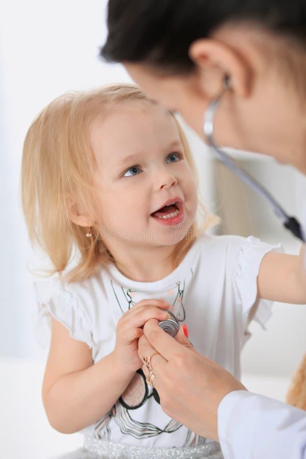 儿科医生在医院照顾婴孩 小女孩是由有听诊器的医生审查 胳膊关心健康查出滞后 库存照片