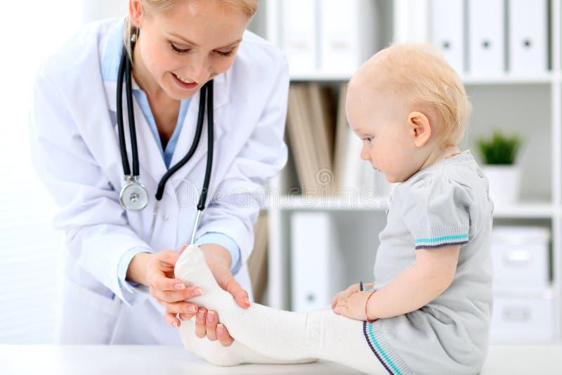 儿科医生在医院照顾婴孩 小女孩是由有听诊器的医生审查 胳膊关心健康查出滞后 免版税库存图片