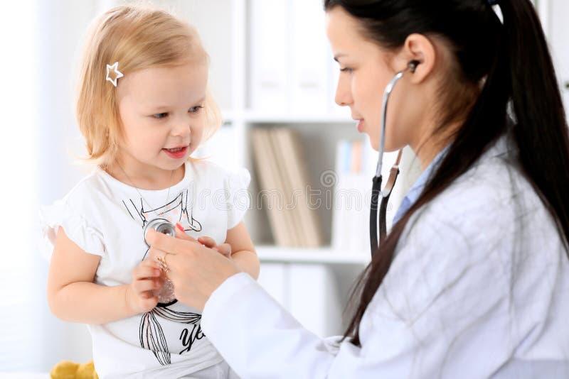 儿科医生在医院照顾婴孩 小女孩是由有听诊器的医生审查 胳膊关心健康查出滞后 库存图片