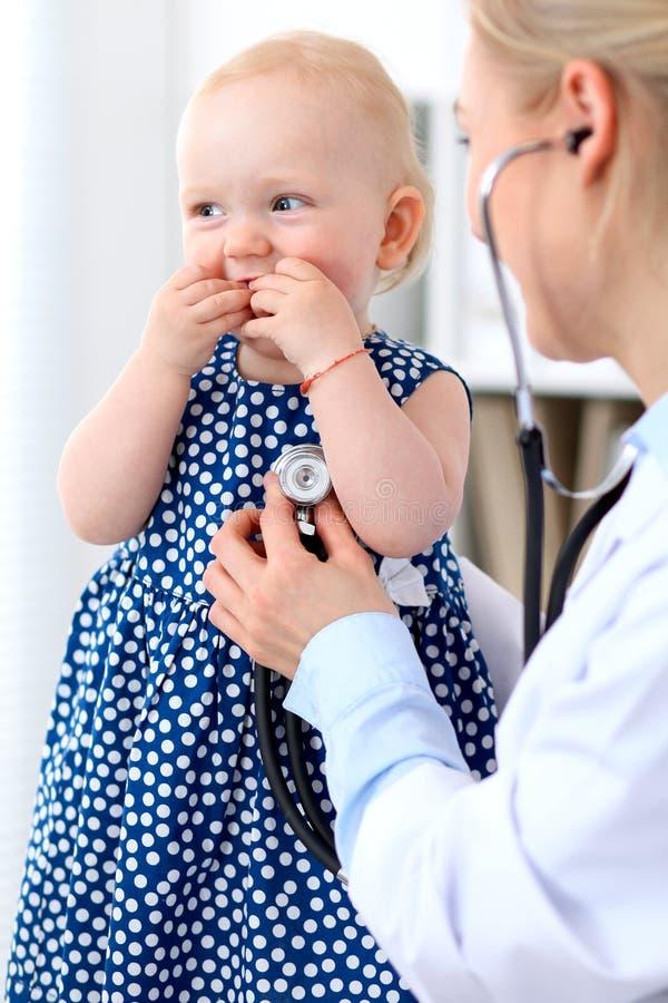 儿科医生在医院照顾婴孩 小女孩是由有听诊器的医生审查 胳膊关心健康查出滞后 图库摄影