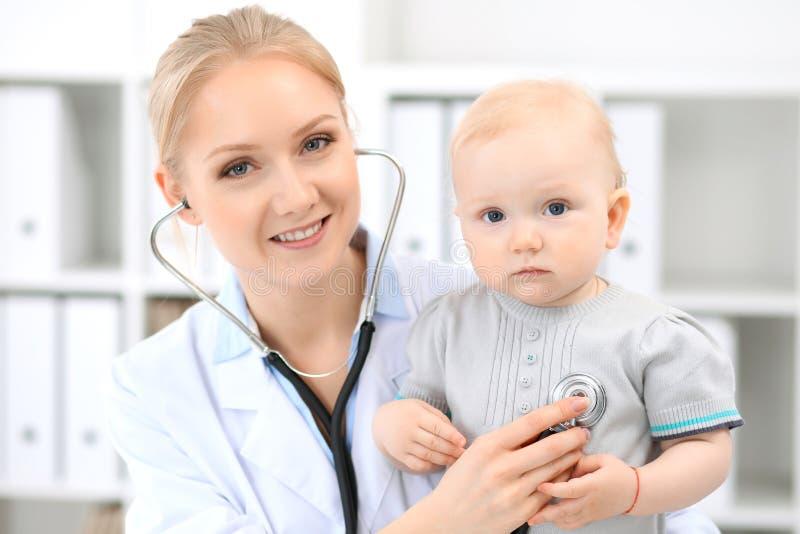儿科医生在医院照顾婴孩 小女孩是由有听诊器的医生审查 库存图片