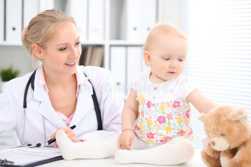 儿科医生在医院照顾婴孩 小女孩是由有听诊器的医生审查 库存照片