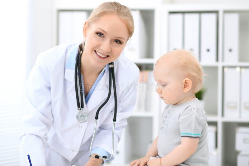 儿科医生在医院照顾婴孩 小女孩是由有听诊器的医生审查 免版税图库摄影