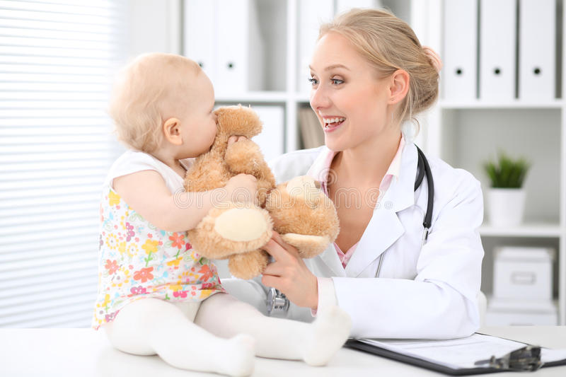 儿科医生在医院照顾婴孩 小女孩是由有听诊器的医生审查 免版税库存图片