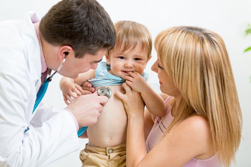 儿科医生男性医生审查的孩子 母亲 免版税库存照片