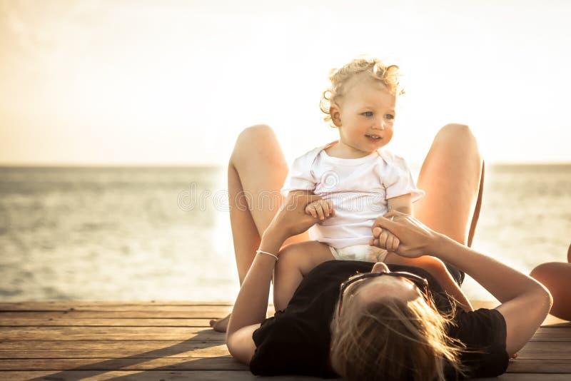 儿童一起放松海滩的小母亲在夏天海滩假日阳光期间 免版税库存图片