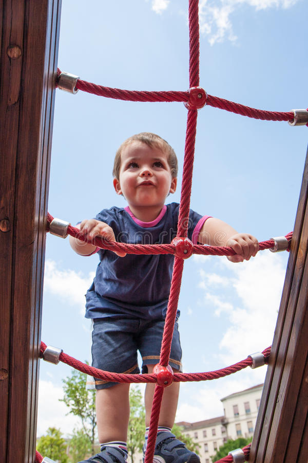 儿童上升的绳索在操场 免版税库存图片