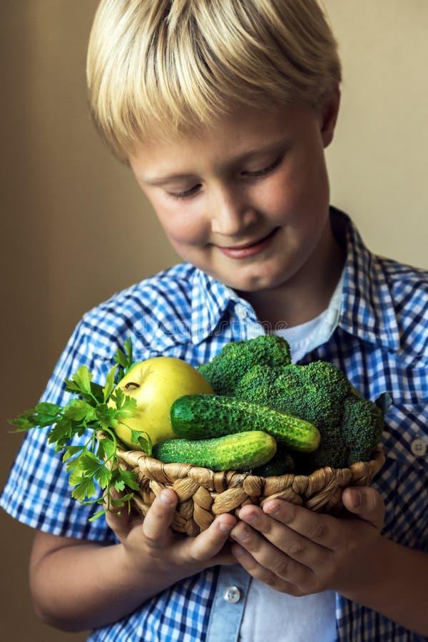 儿童与绿色菜的举行篮子 免版税图库摄影