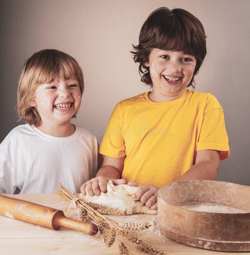 儿童两兄弟和一起揉面团 免版税库存图片