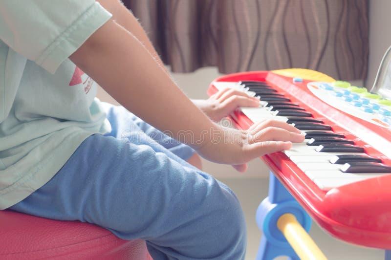 儿童亚洲演奏电子键盘的实践手指戏弄 免版税库存图片