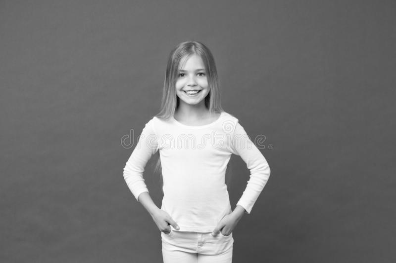 儿童佩带的白色套头衫和牛仔裤,青年时尚概念 有长期发光的金发女孩 与大的可爱的孩子 免版税库存图片