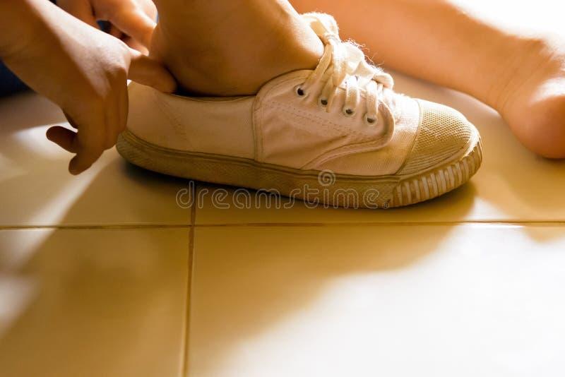 儿童佩带的鞋子在他的房子里 放大 免版税图库摄影