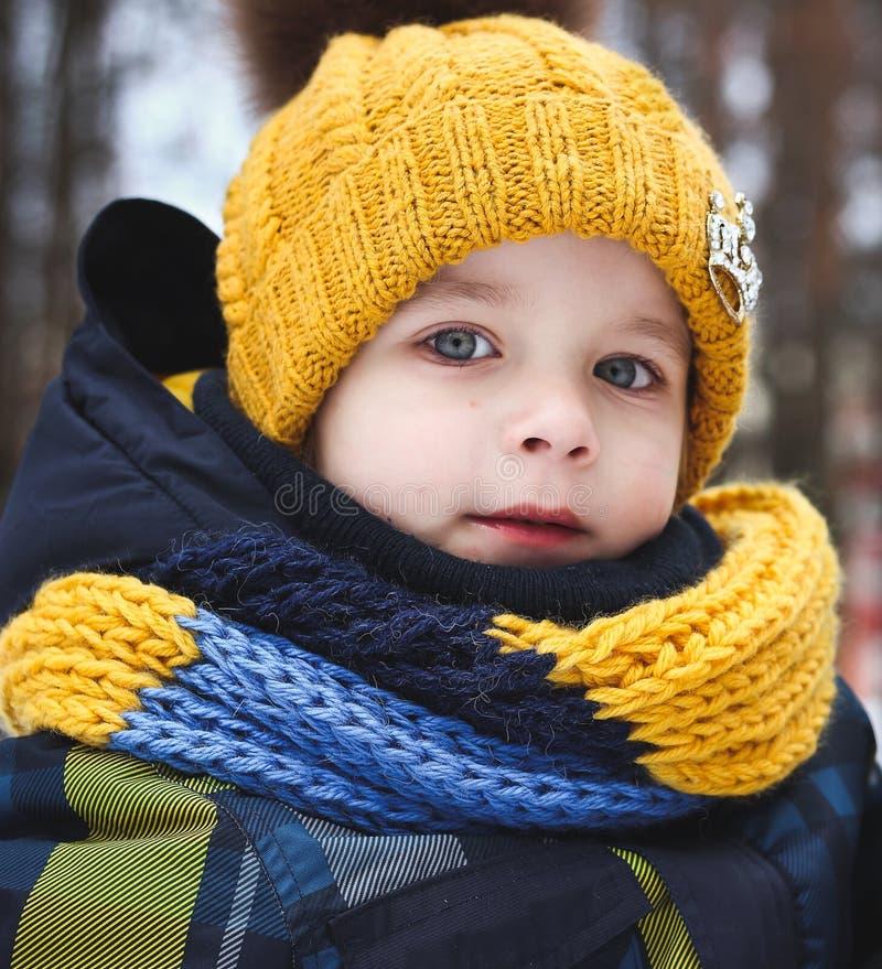 步行的小男孩在冬天黄色盖帽图片