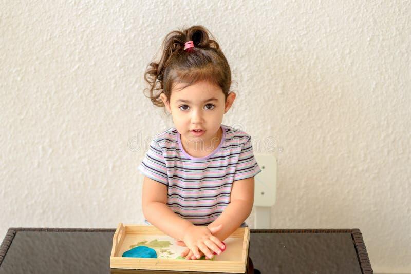 儿童创造性 孩子从黏土雕刻 逗人喜爱的女孩从在桌上的彩色塑泥铸造 免版税库存图片