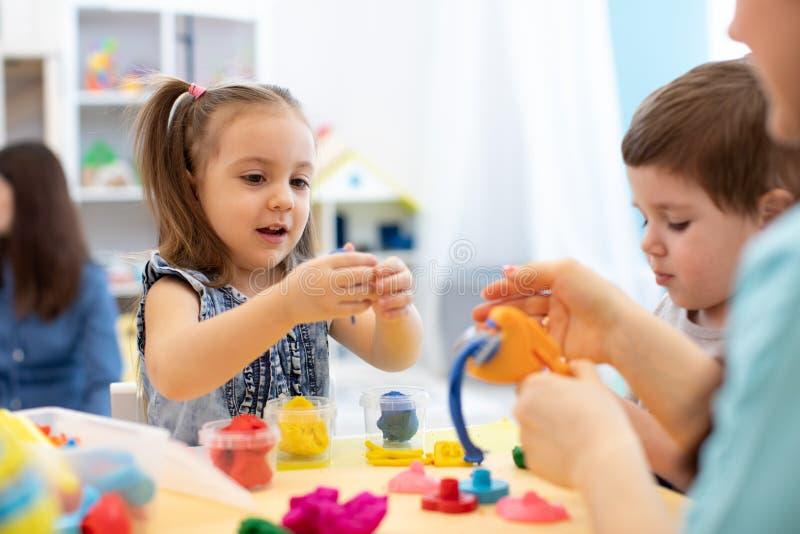 儿童创造性 雕刻从黏土的孩子 从彩色塑泥的逗人喜爱的女孩模子在桌上在幼儿园 免版税库存图片