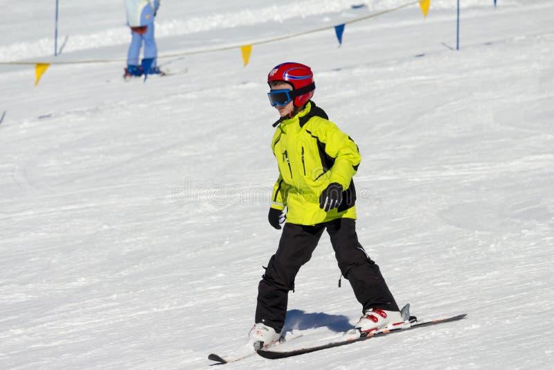 儿童初学者在雪的滑雪倾斜 免版税图库摄影