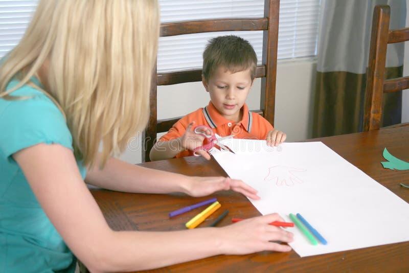 儿童剪切纸张剪妇女 图库摄影