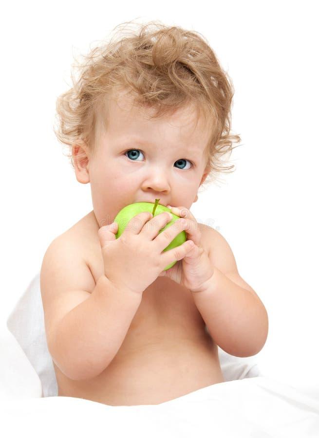 儿童卷发的画象吃一个绿色苹果 库存照片