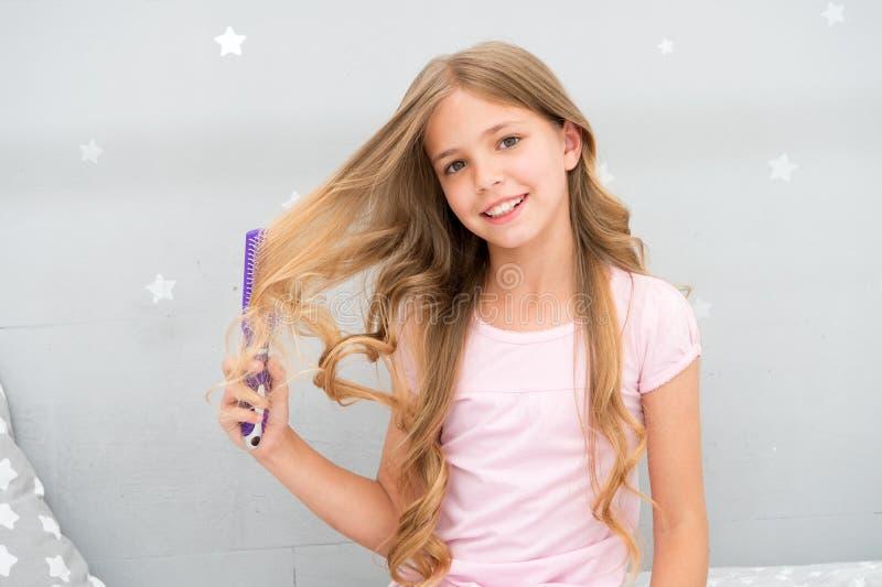 儿童卷曲发型举行发刷或梳子 以前梳子头发去睡 理发习性概念 调节剂或 库存照片