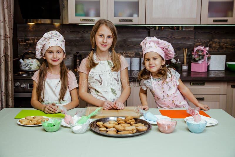 儿童厨房女孩烹调围裙杯形蛋糕曲奇饼小滑稽的三个姐妹盖帽奶油奶油装饰 免版税库存照片