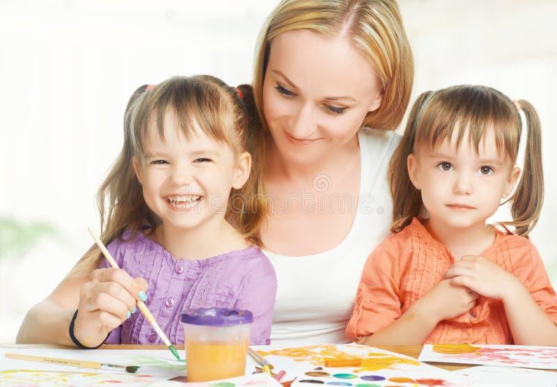 儿童双姐妹在白色背景的幼儿园画与她的母亲的油漆 免版税库存图片