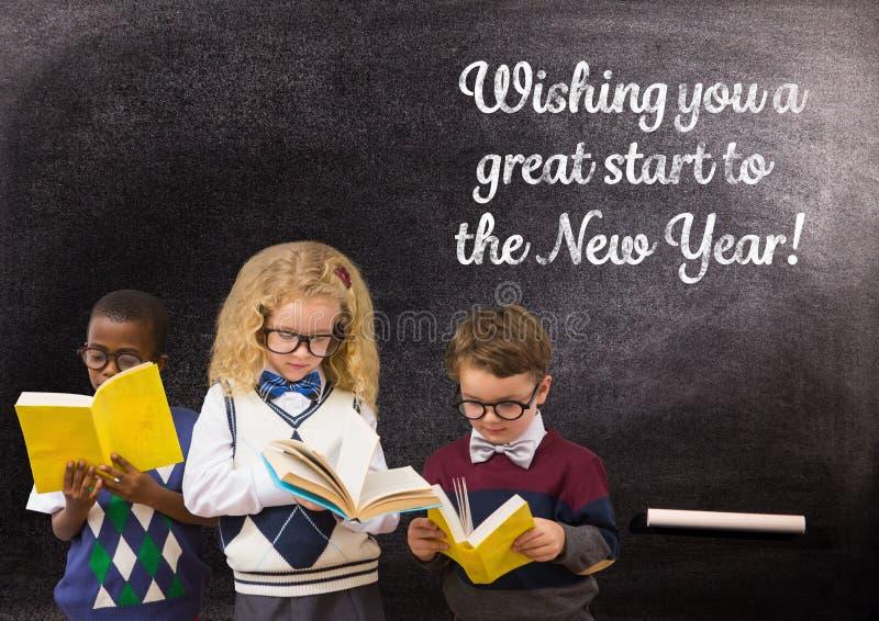 儿童反对黑板的阅读书有2017新年问候的引述 免版税图库摄影