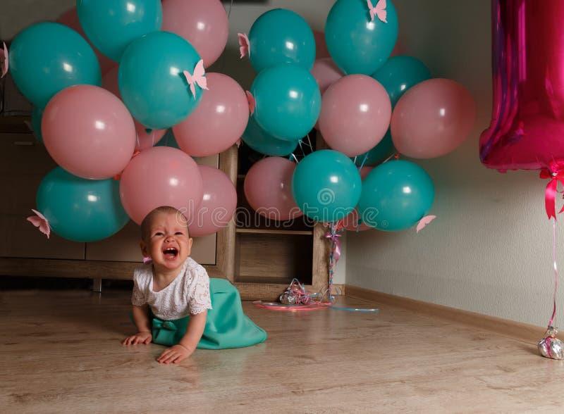 儿童啼声,生气,一个小女孩,孩子,坐地板和啼声,起皱纹她的鼻子,在气球附近,一个假日 免版税图库摄影