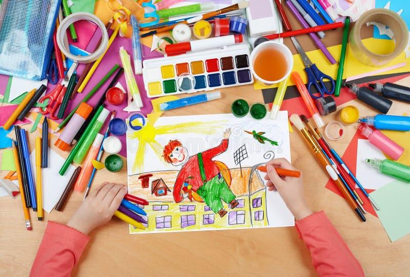 儿童图画与空气螺旋桨的男孩飞行在他的,有铅笔绘画图片的顶视图手在纸,艺术品工作场所 免版税库存图片