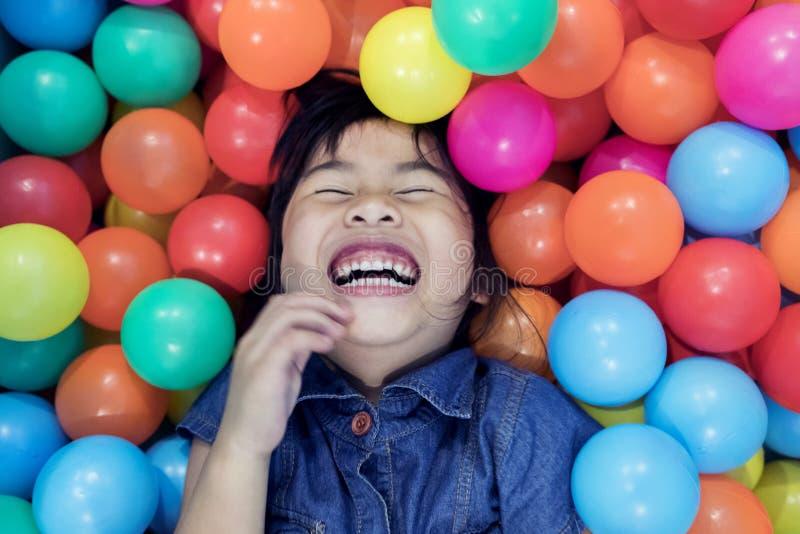 儿童在五颜六色的幸福情感在球水池 免版税库存照片