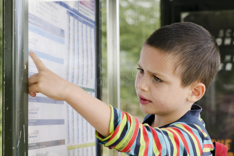 儿童在公共汽车站的读书时间表 库存图片