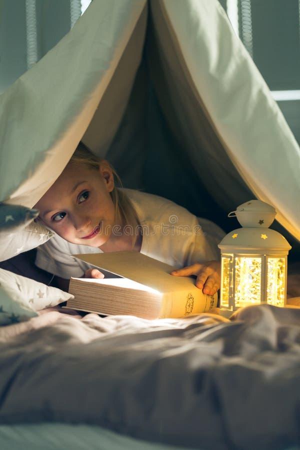 儿童在帐篷的阅读书 免版税库存照片